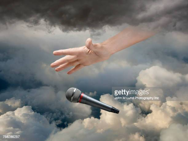 Caucasian hand dropping microphone in clouds