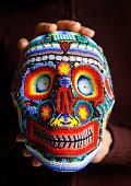 Caucasian hand holding colorful beaded skull