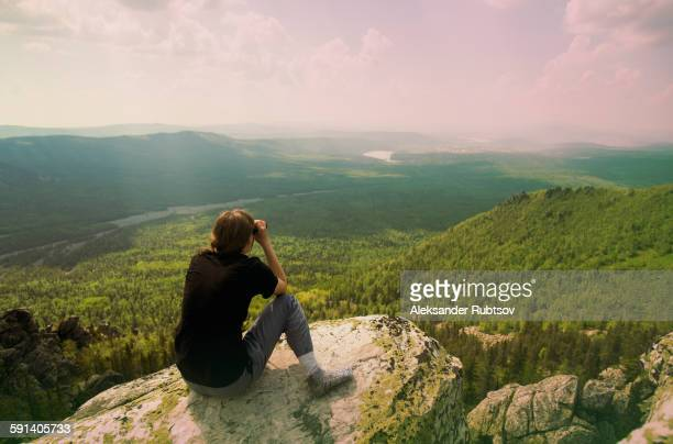 Caucasian hiker admiring remote landscape from rocky hilltop