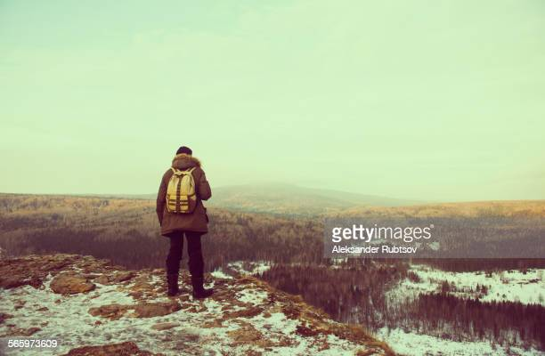 Caucasian hiker admiring scenic view from snowy mountaintop