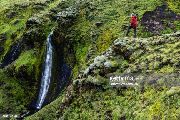 Caucasian hiker admiring waterfall and rock formations on mountainside