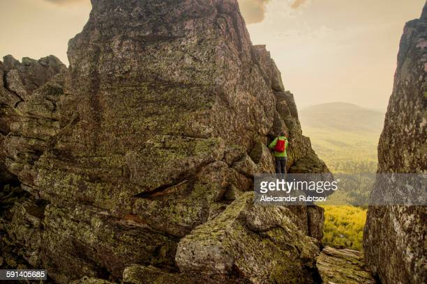 Caucasian hiker climbing on rock formation