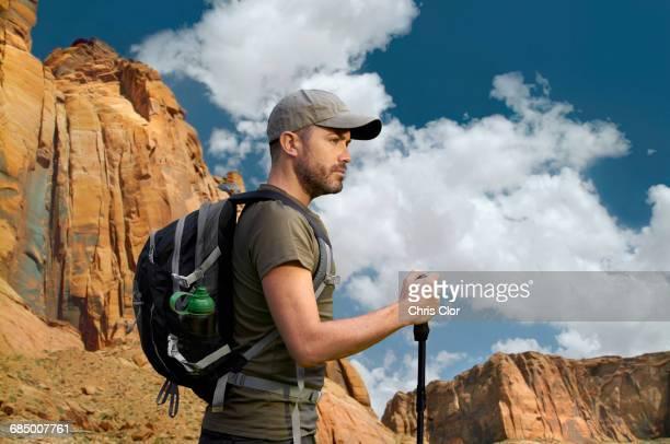 Caucasian hiker holding walking stick in desert landscape