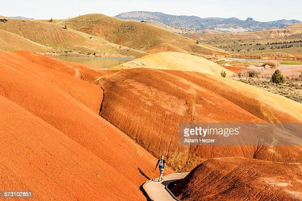 Caucasian hiker on wooden walkway in desert hills