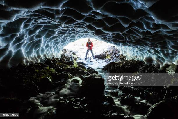 Caucasian hiker viewing stream from entrance of ice cave