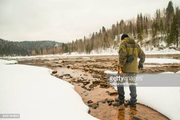 Caucasian hiker walking in rocky remote river