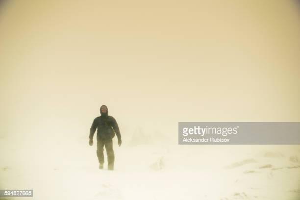 Caucasian hiker walking in snow
