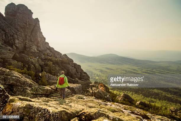 Caucasian hiker walking on rocky hillside in remote landscape
