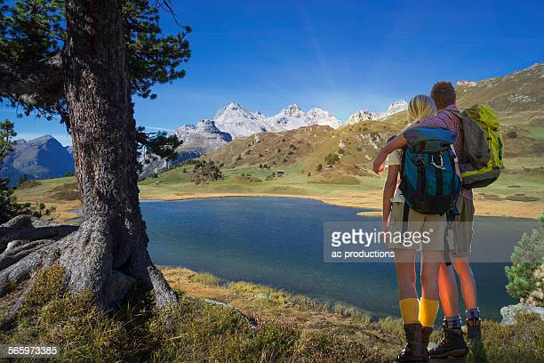Caucasian hikers admiring remote lake, Lai da Vons, Canton Graubunden, Switzerland
