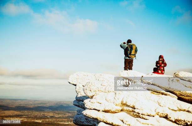 Caucasian hikers admiring scenic view from mountaintop