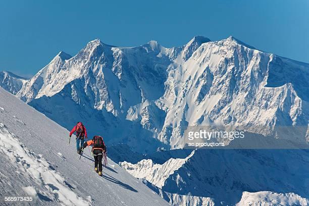Caucasian hikers climbing snowy mountain, Monte Rosa, Piedmont, Italy