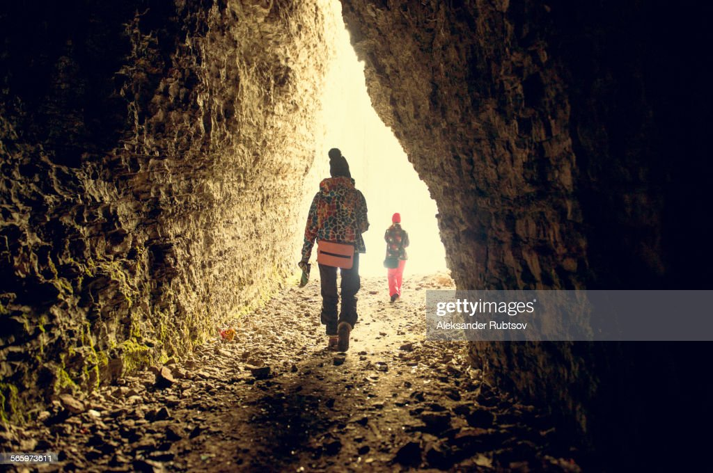 Caucasian hikers walking in rocky cave : Stock Photo