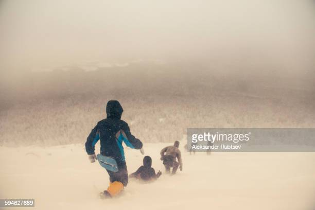 Caucasian hikers walking on snowy hill