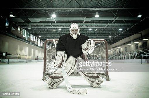 Caucasian hockey goalie standing near net