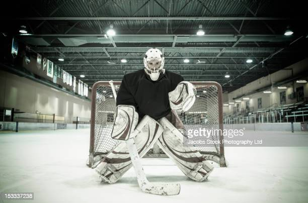 Caucasian hockey goalie standing near net