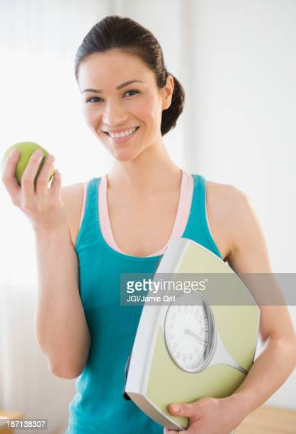 Caucasian holding apple and scale
