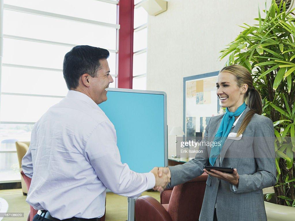 Caucasian hostess greeting businessman