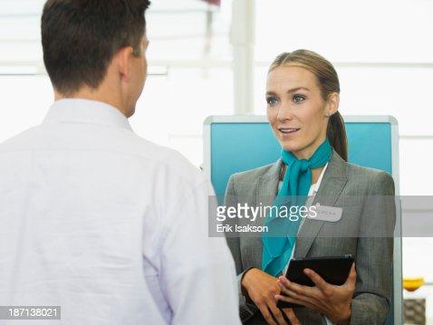 Caucasian hostess talking to businessman : Stock Photo