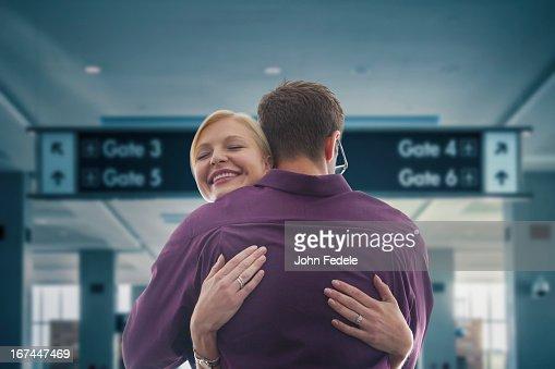 Caucasian hugging in airport : Stock Photo