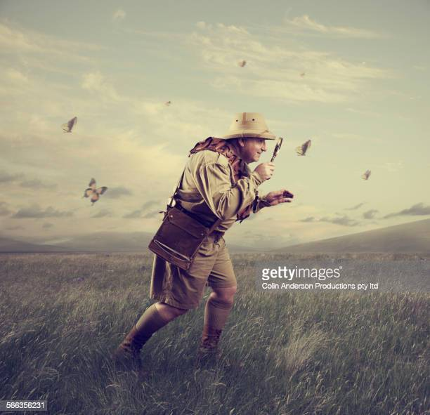 Caucasian hunter examining butterfly with magnifying glass
