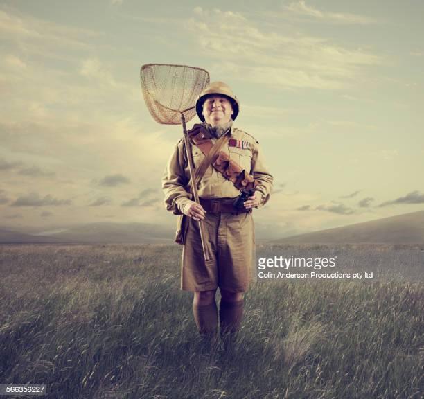 Caucasian hunter holding net in remote field