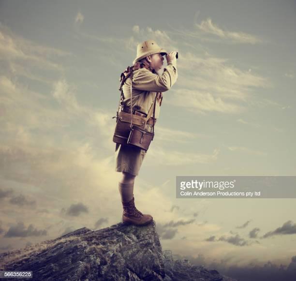 Caucasian hunter using binoculars on mountaintop