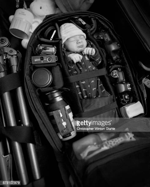 Caucasian infant packed into camera bag