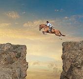 Caucasian jockey jumping canyon on horse