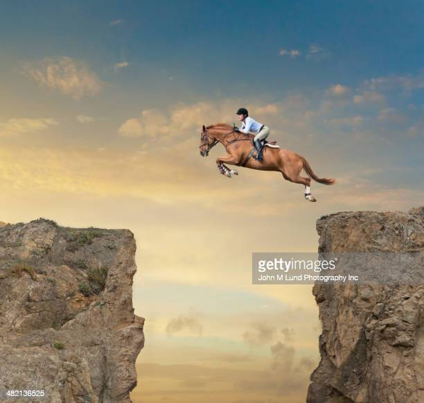 Caucasian jockey jumping canyon on horse