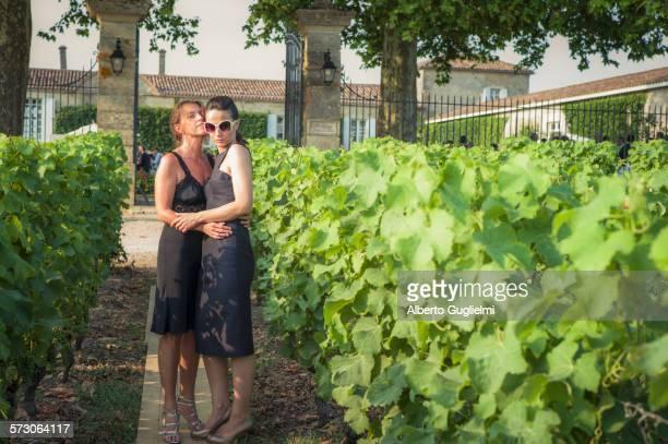 Caucasian lesbian couple hugging in vineyard