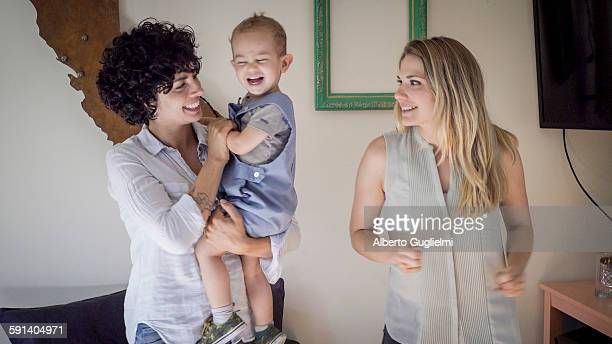 Caucasian lesbian mothers and baby son in living room