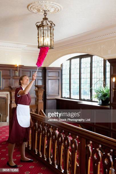 Caucasian maid dusting chandelier in hotel hallway