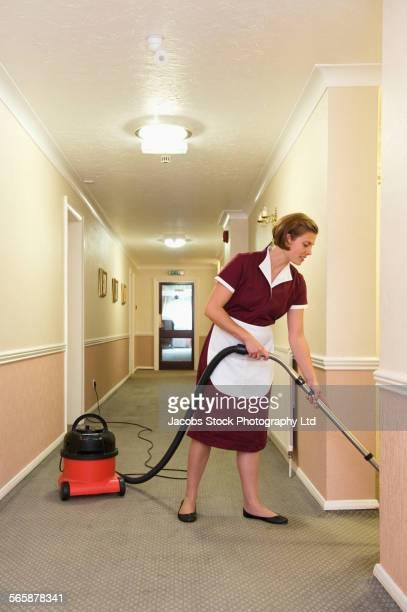 Caucasian maid vacuuming hotel hallway