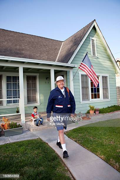 Caucasian mailman walking in front yard