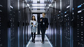 Caucasian Male and Asian Female IT Technicians Walking through Corridor of Data Center with Rows of Rack Servers. They Have Discussion, She Holds Tablet Computer.