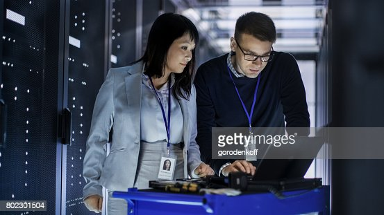 Caucasian Male and Asian Female IT Technicians Working with Computer Crash Cart in Big Data Center full of Rack Servers. : Stock Photo