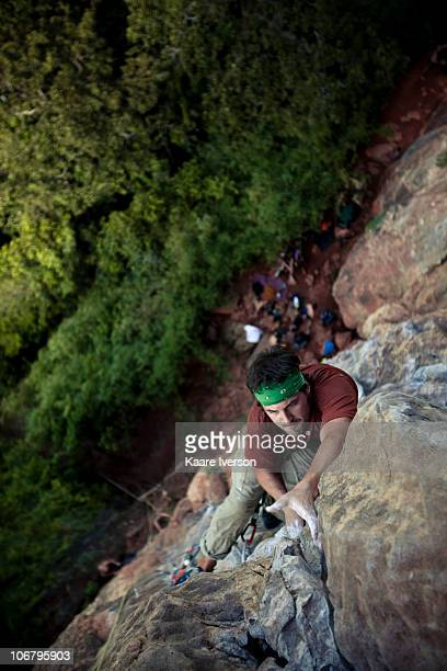 Caucasian male climber reaches out to a final hold high above the jungle in Thailand.