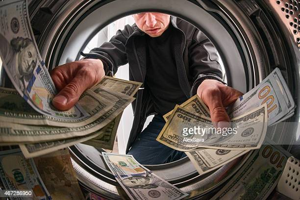 Caucasian male criminal throwing money inside a laundry machine