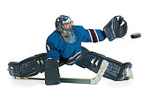 A caucasian male hockey goalie in a blue uniform splits his legs and reaches for the puck to block a shot