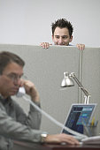 Caucasian Male Office Worker Peeking Over The Cubicle Wall At His Coworker