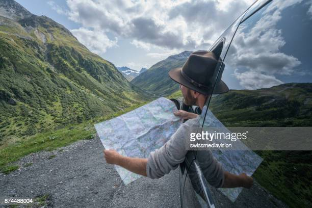 Caucasian male on road trip looks at map, mountain landscape