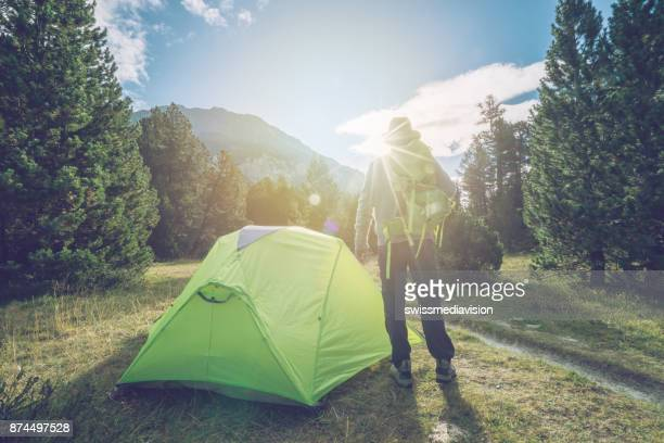 Caucasian male relaxing beside tent at sunset, Switzerland
