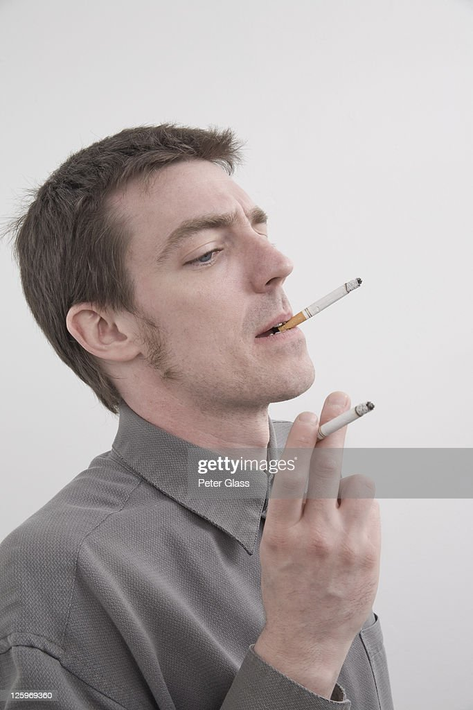 Caucasian male (31 years old) smoking two cigarettes : Stock Photo