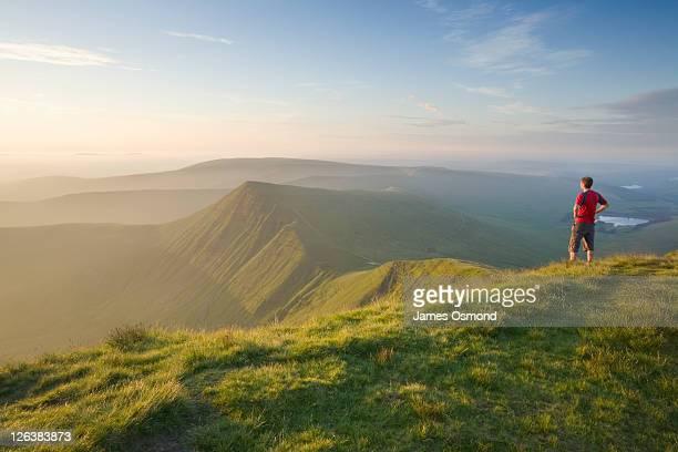 Caucasian Male Walker (30 years old) on Pen y Fan summit at sunrise looking towards Cribyn, Brecon Beacons National Park, Powys, Wales UK
