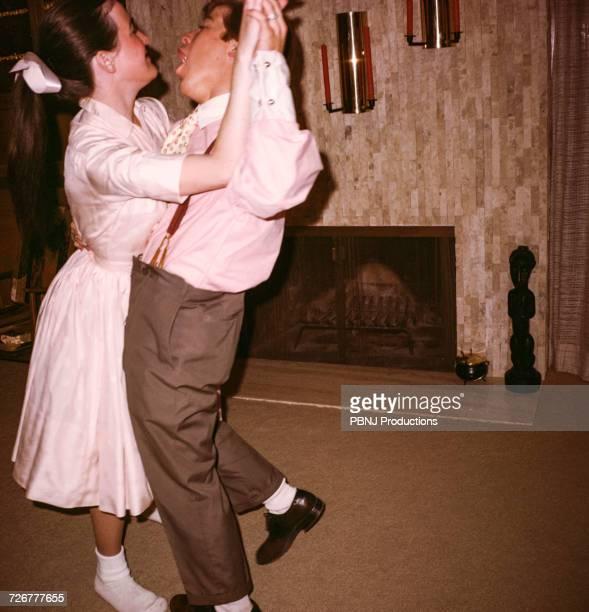Caucasian man and woman dancing near fireplace
