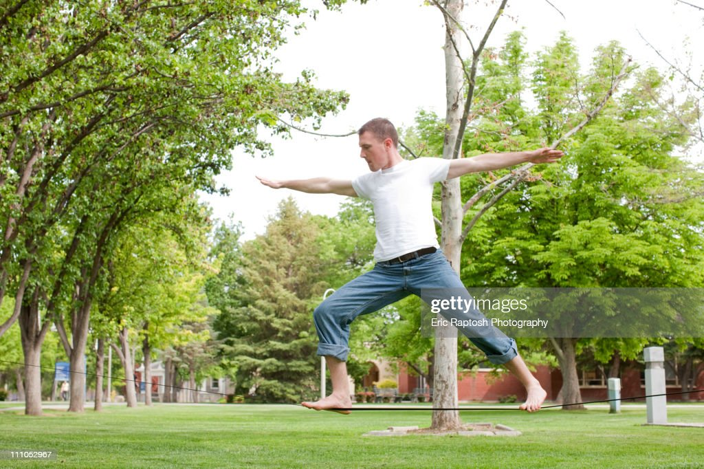 Caucasian man balancing on rope in park : Stock Photo