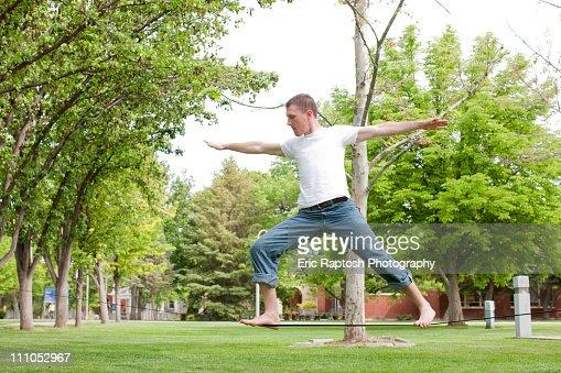 Caucasian man balancing on rope in park : Bildbanksbilder