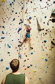 Caucasian man belaying climber at indoor rock wall