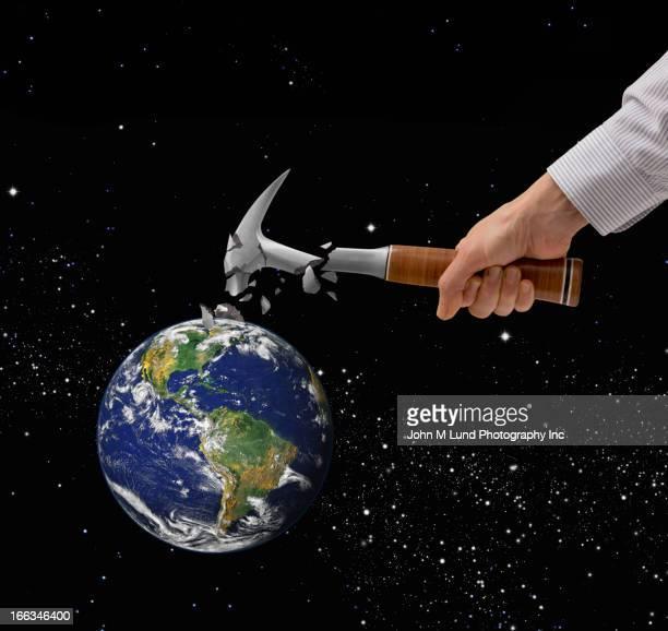 Caucasian man breaking hammer on planet earth