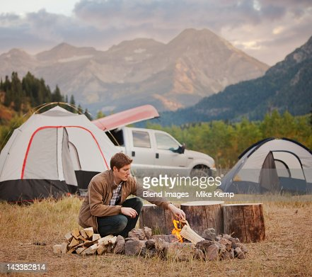 Caucasian man building campfire at campsite : Stock Photo
